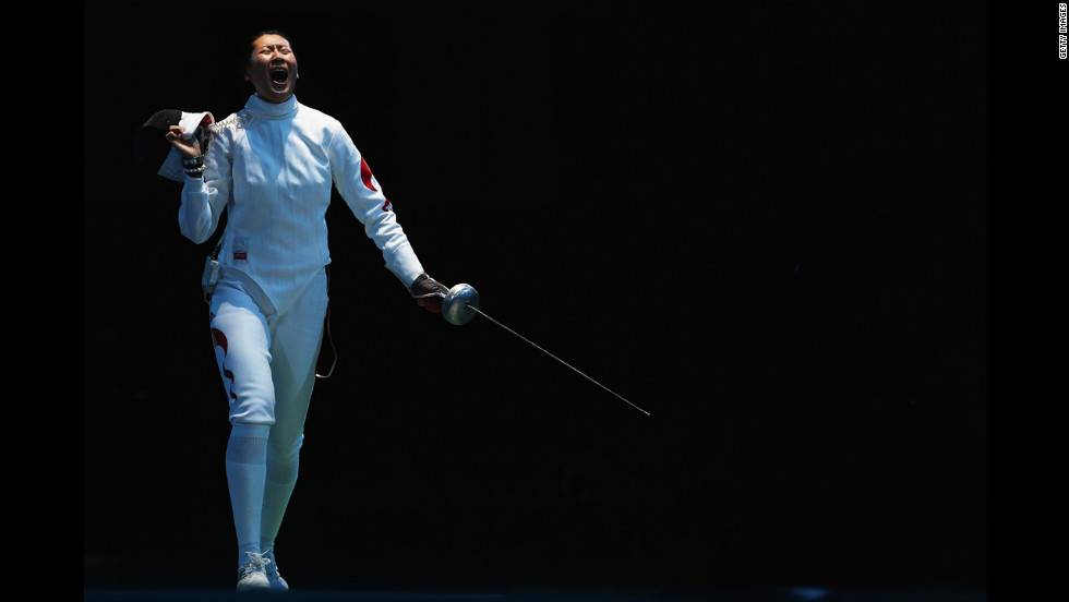 Yujie Sun of China celebrates after beating Britta Heidemann of Germany during the women's epee team fencing quarterfinals.