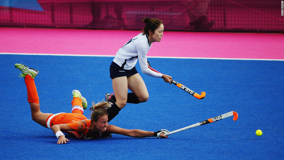 Captain Maartje Paumen of the Netherlands challenges Kim Jong Hee of South Korea during a women's hockey match.