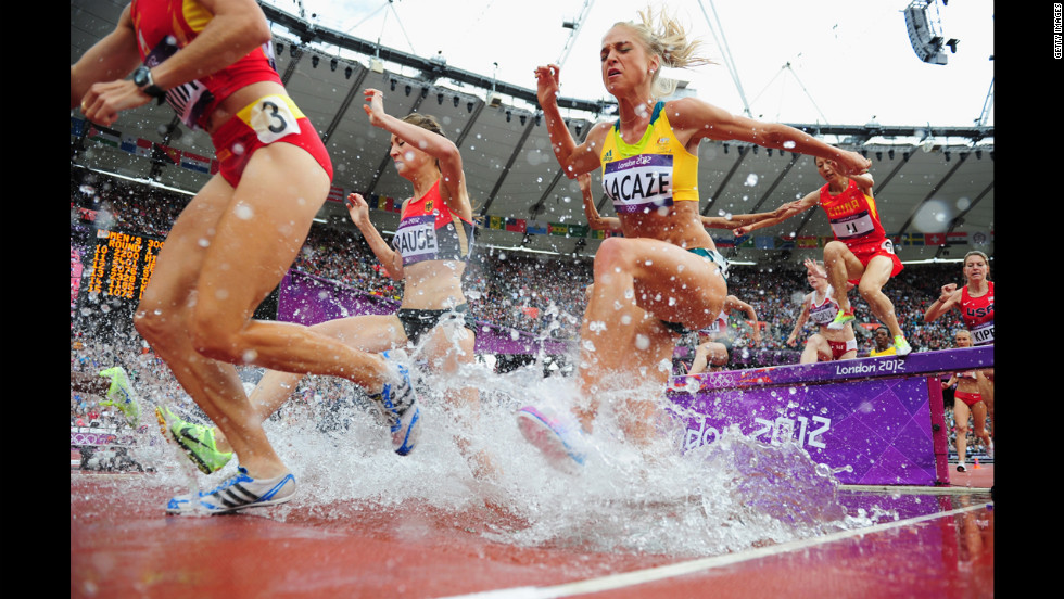 Runners compete in a women's 3000-meter steeplechase heat at Olympic Stadium.