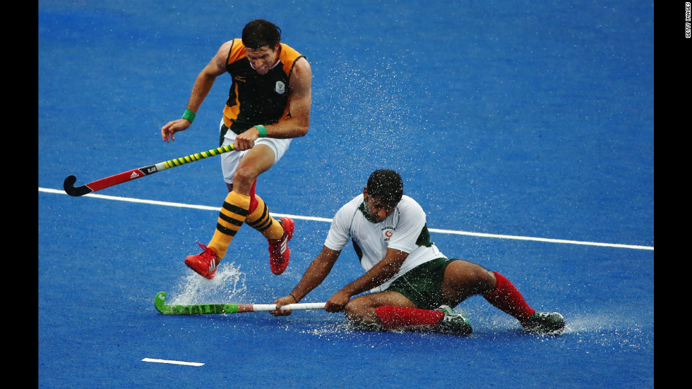 Thornton McDade of South Africa and Muhammad Imran of Pakistan challenge for the ball during a men's field hockey match.