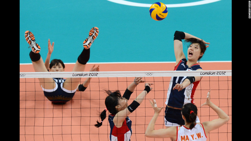 South Korea's Yang Hyo-Jin, top right, spikes as China's Ma Yunwen, bottom right, attempts to block during the women's preliminary pool B volleyball match.