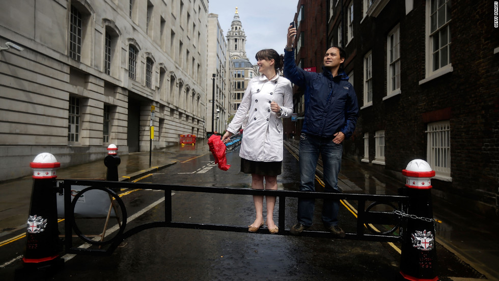 Despite the rain, two spectators eagerly await a view of runners in the women's marathon near St. Paul's Cathedral in London.
