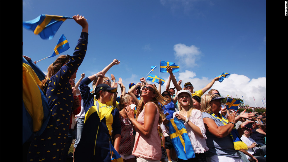 Supporters of Fredrik Loof and Max Salminen of Sweden celebrate as the sailors take overall victory following the men's star sailing medal race.