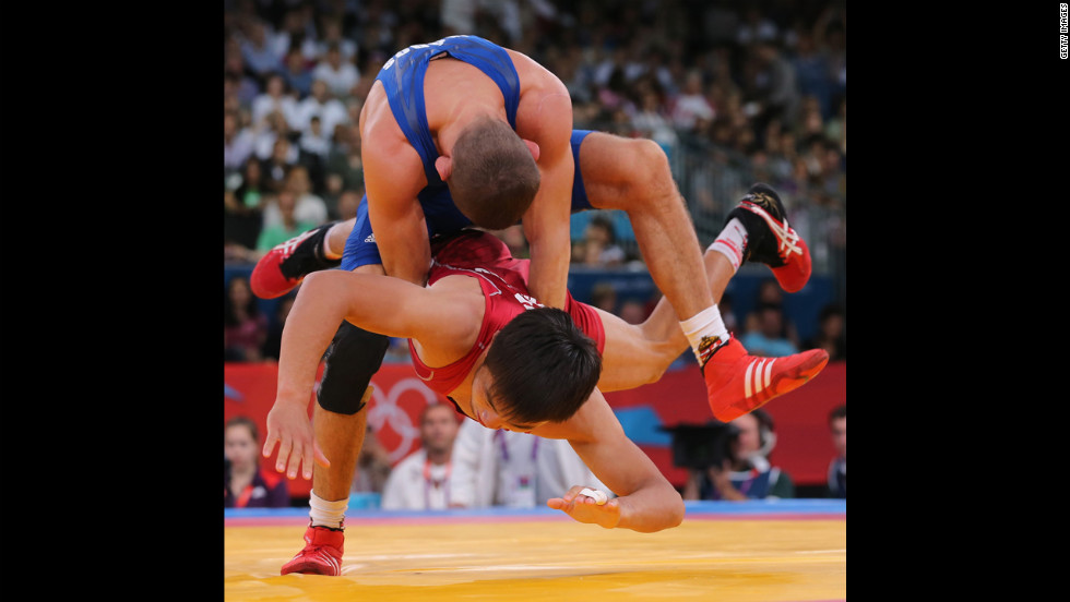 Peter Modos of Hungary, top, wrestles with Arsen Eraliev of Kyrgyzstan, bottom, during the men's Greco-Roman 55-kilogram wrestling qualification.