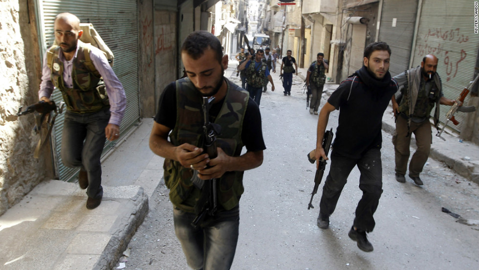 A Syrian rebel prepares his weapon as a group of Free Syrian Army fighters head toward the fighting with Syrian Army soldiers in the Salah ad-Din neighborhood of central Aleppo on Sunday, August 5.