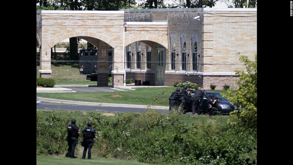 SWAT officers gather in front of the temple Sunday. The attack occurred about 10:30 a.m., when temple members were reading scriptures and cooking food.