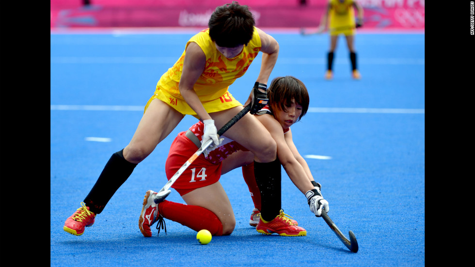 Gao Lihua of China, in yellow, is tackled by Manabe Kieko of Japan during the women's field hockey preliminary round match.