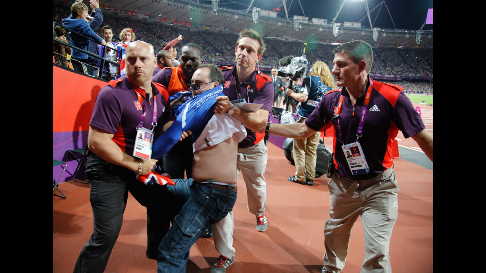 A spectator is detained by security after a beer bottle was thrown onto the track during the start of the men's 100-meter final.