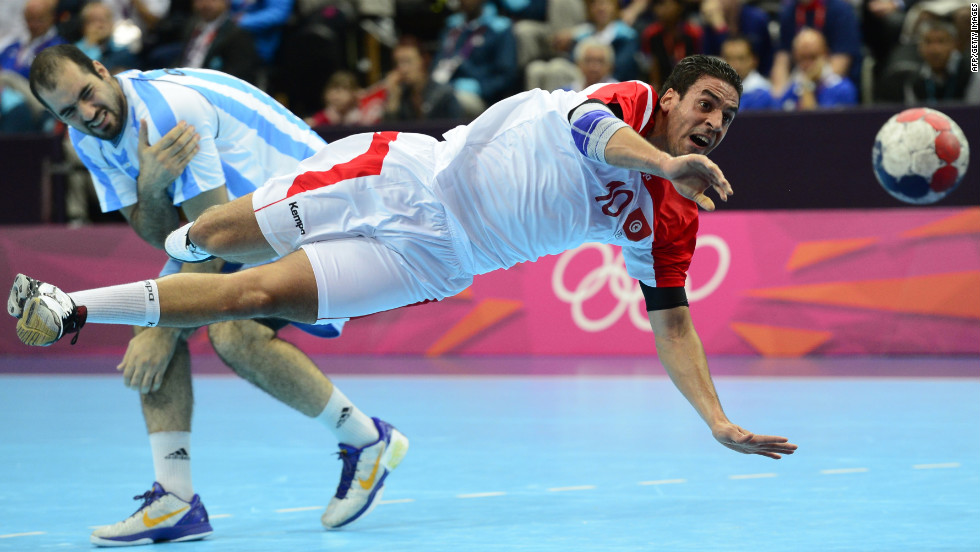 Tunisian centerback Kamel Alouini, right, jumps and shoots past Argentina's Leonardo Facundo Querin during the men's preliminary Group A handball match.