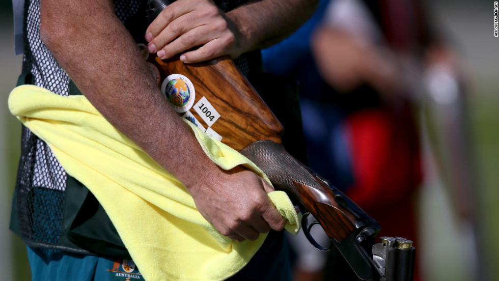 Michael Diamond of Australia wipes down his gun as he competes in the men's trap shooting qualification at the Royal Artillery Barracks Excel Centre.