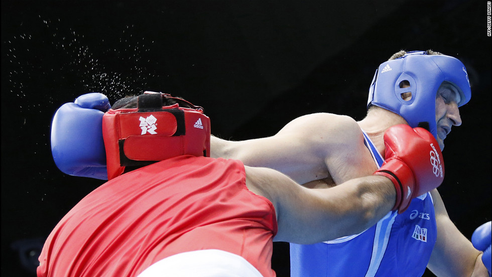 Mohammed Arjaoui of Morocco, in red, and Roberto Cammarelle of Italy, in blue, trade punches during their super heavyweight boxing quarterfinal.