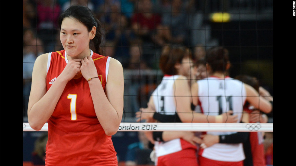 Chinese volleyball player Wang Yimei reacts as the Japanese team celebrates after it won the third set women's quarterfinal match. Japan won in five sets.