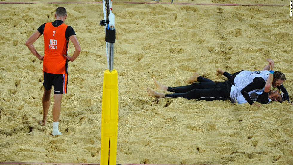 Rich Schuil of Netherlands looks dejected as Julius Brink and Jonas Reckermann of Germany celebrate match point during the men's beach volleyball semifinal match between Germany and the Netherlands.