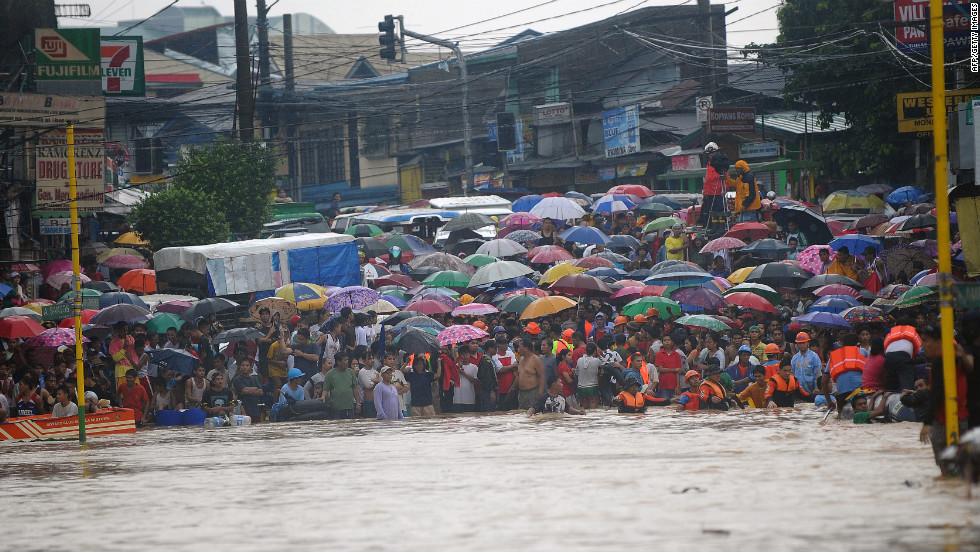 Residents wait for family members to be rescued at the end of a flooded street in the village of Tumana, a suburb of Manila on Tuesday, August 7.