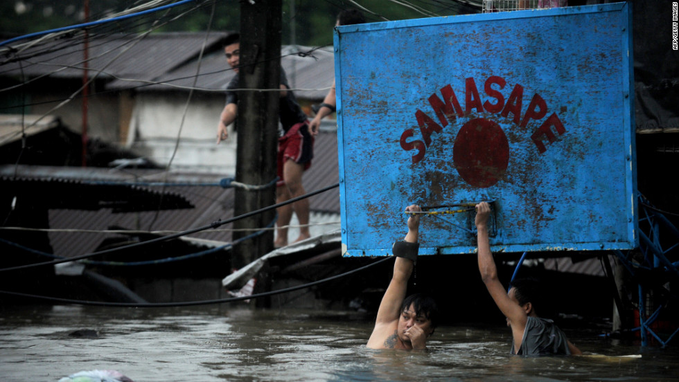 Two men hang onto a basketball hoop in deep floodwaters in Manila.