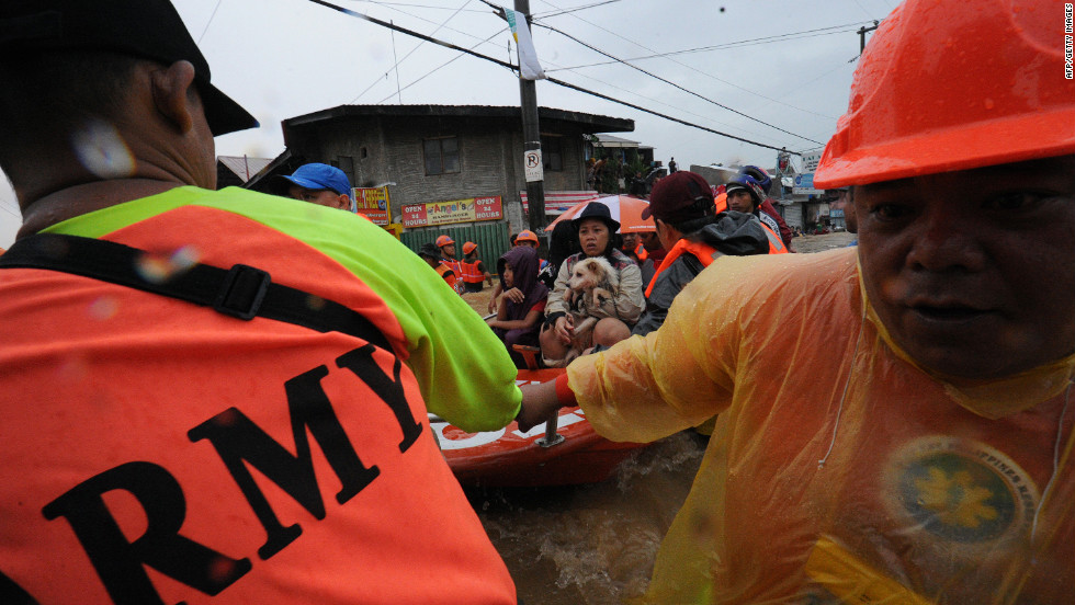 Rescue workers prepare to unload residents in the village of Tumana after their homes were flooded.