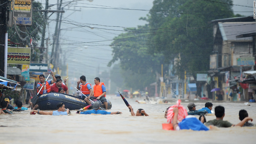 Residents wait on the roofs of buildings as rescuers make their way down a flooded street in Tumana.