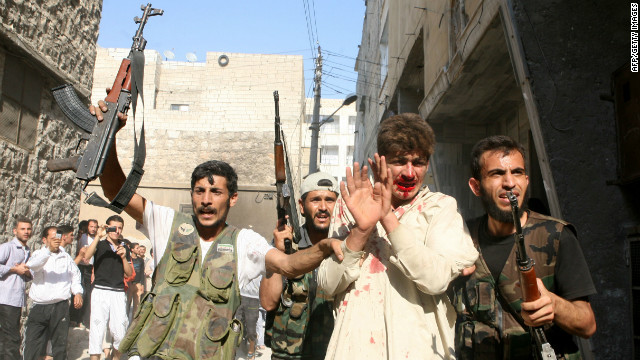 Rebel Free Syrian Army fighters march a captured policeman who they believe is a pro-regime militiaman on July 31, 2012.