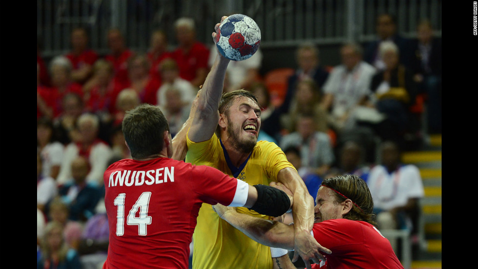 Sweden's right back Kim Andersson, center, vies with Denmark's pivot Michael Knudsen during the men's quarterfinal handball match.