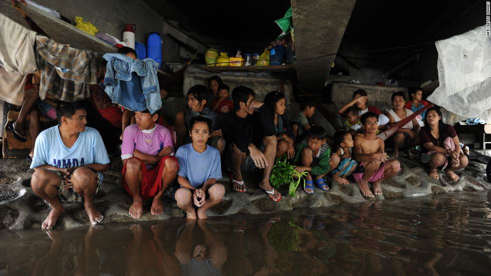 A group of Filipino farm workers huddles beneath a bridge north of Manila on Wednesday. Flooding caused by 10 days of torrential rains, worsened by the overflowing of three dams, has paralyzed 80% of the city. More than 70 people have died and 263,000 residents have been displaced.