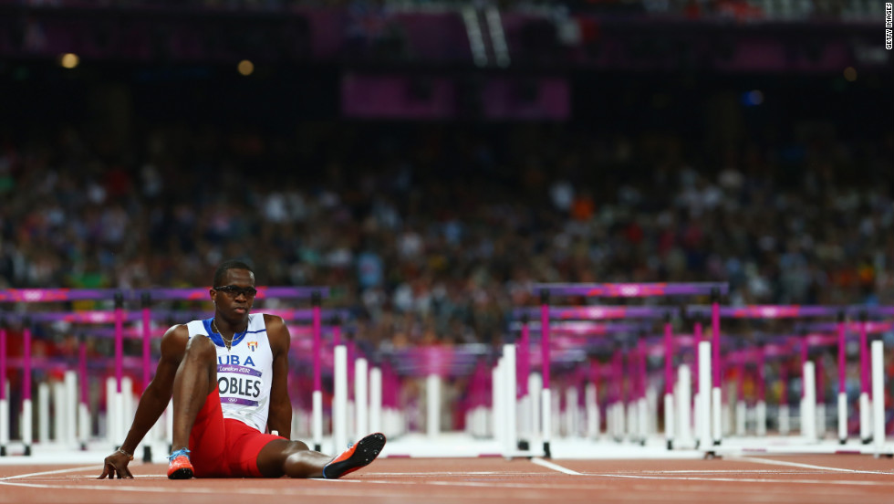 Dayron Robles of Cuba waits on the track after pulling up injured in the men's 110-meter hurdles final.