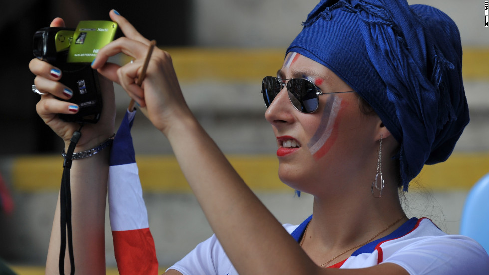 A fan of the French football team snaps some action during the women's football match for bronze between France and Canada.