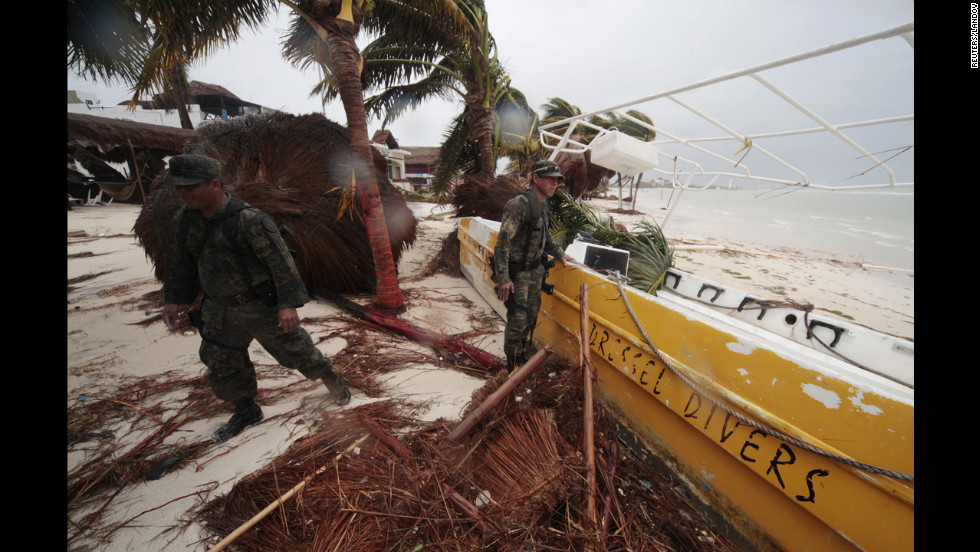 Soldiers stand amid debris left after the passing of Hurricane Ernesto in Mahahual, Mexico, on Wednesday, August 8. After crossing the Yucatan Peninsula, the storm is expected to make landfall a second time on Mexico's coast by Thursday evening.