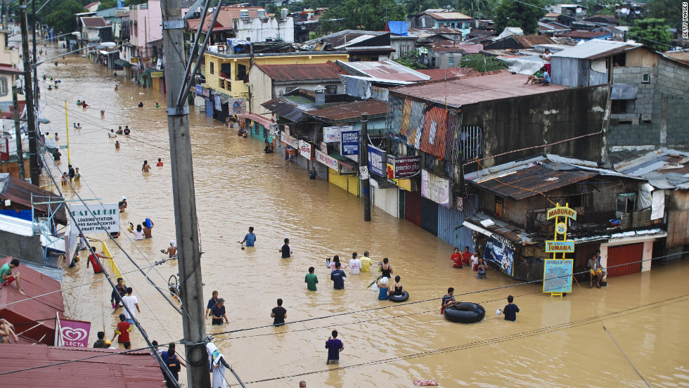 Residents cross floodwaters Wednesday during heavy flooding in Manila.