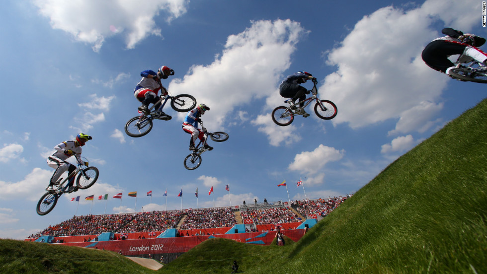 Bikers leap through the course in the men's BMX cycling quarterfinals.