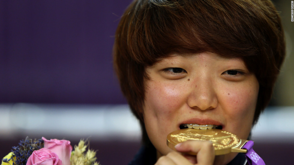 South Korea's Kim Jang-mi bites her gold medal on the podium after victory in the women's 25-meter pistol final.