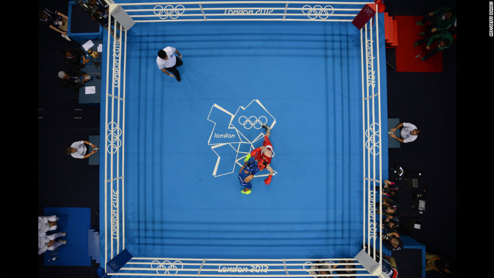 Paddy Barnes of Ireland, in red, defends against Devendro Singh Laishram of India, in blue, during the light flyweight boxing quarterfinals.