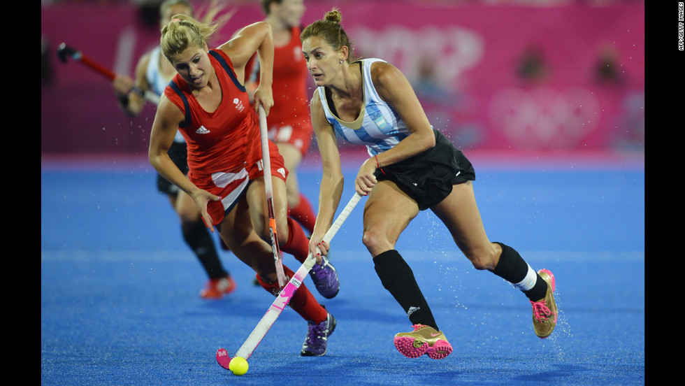 Argentina's Luciana Aymar, right, rushes past Britain's Georgie Twigg, in the women's hockey semifinal.
