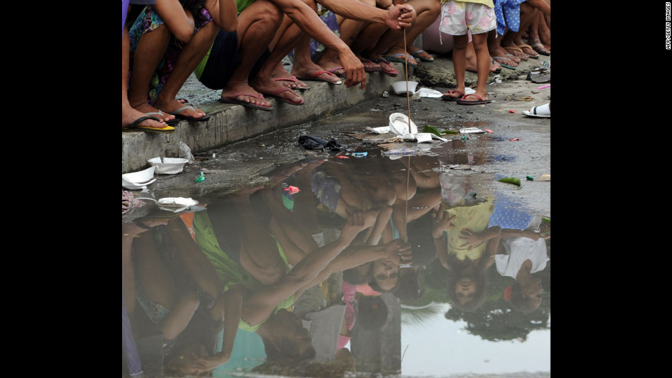 Residents line up for relief goods to arrive Friday in Malabon, a suburb of Manila. It's monsoon season in the Philippines, but the recent Tropical Storm Haikui has exacerbated the rain and flooding.