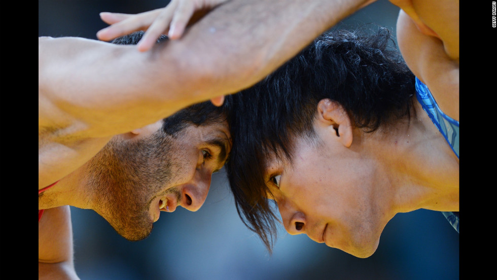 Azerbaijan's Ashraf Aliyev, left, grapples with Sohsuke Takatani of Japan in the men's freestyle 74-kilogram wrestling.