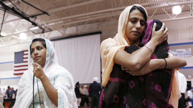 Mourners hug as community members pay respect to the six people killed at the Sikh Temple of Wisconsin.