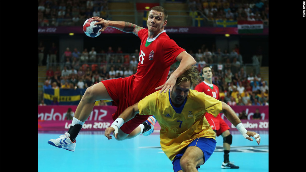 No. 25 Szabolcs Zubai of Hungary shoots over No. 7 Magnus Jernemyr of Sweden during the men's handball semifinal game.