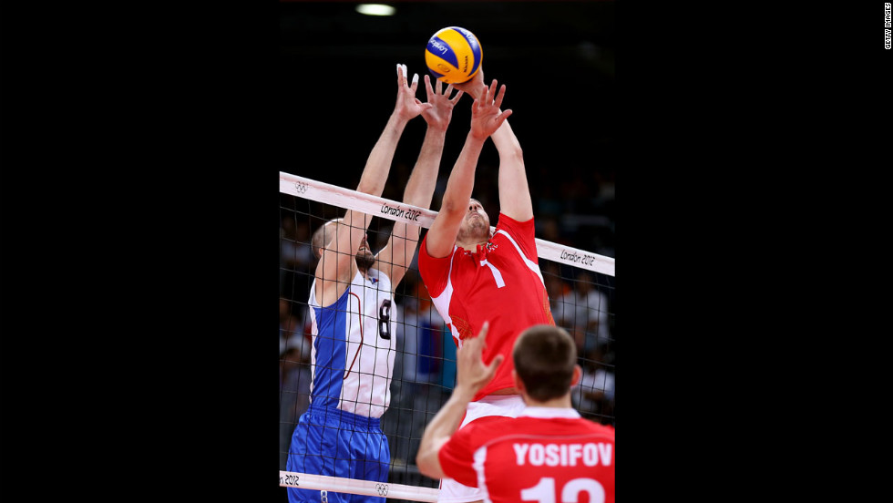 No. 1 Georgi Bratoev of Bulgaria tries to tip the ball over the net against No. 8 Sergey Tetyukhin of Russia during the men's volleyball semifinals.