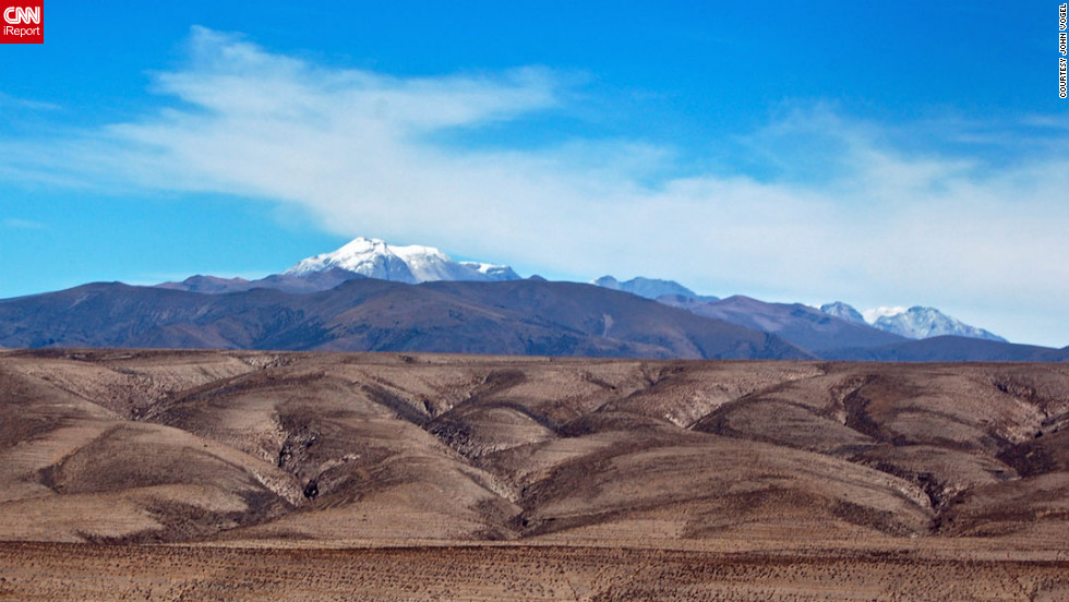 "<a href=""http://ireport.cnn.com/docs/DOC-825313 "">John Vogel</a> was on a minibus traveling between the city of Arequipa and Colca Canyon in Peru when he saw this odd landscape. ""Looking at the photo now, it almost looks like two photos combined into one photo. That's how great I find the contrast between the dark rocky foreground and the bright blue sky with the snow-capped volcano."""