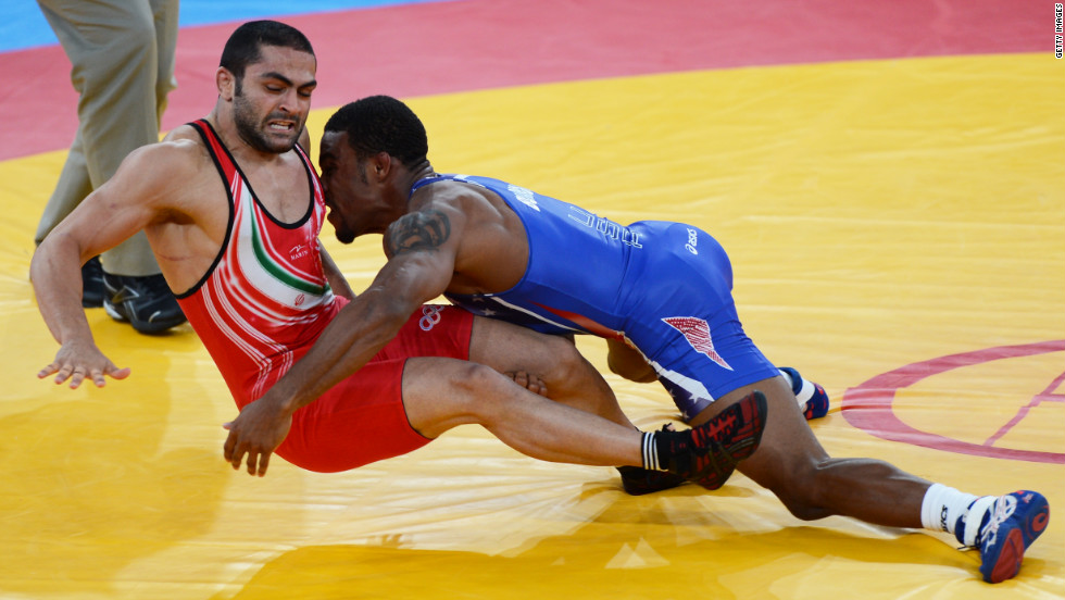 Burroughs, in blue, grapples with Goudarzi in the gold medal match.