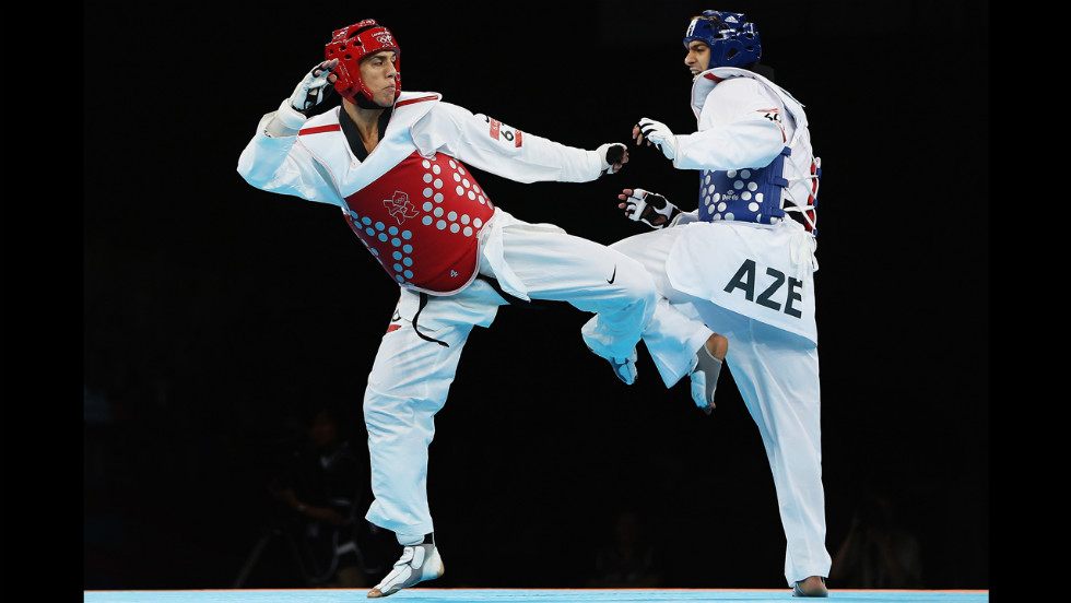 American Steven Lopez, left, competes against Ramin Azizov of Azerbaijan during the men's under 80-kilogram taekwondo preliminary round.