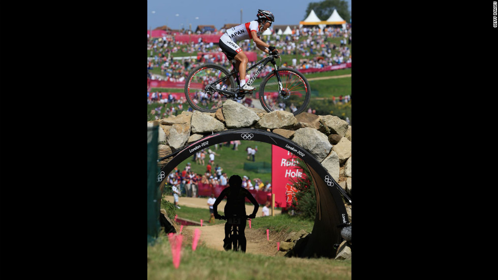 Austrian rider Elisabeth Osl rides under a bridge as Japanese rider Rie Katayama crosses over during the women's cross-country mountain bike race.