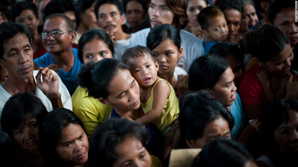 A woman holds a crying baby as she and thousands of flood victims line up for food relief at a municipal building in Paombong.