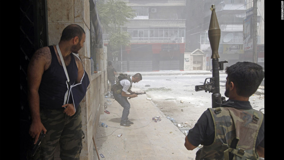A Free Syrian Army fighter tries to fix his jammed rifle during heavy fighting in the Salaheddine neighborhood.