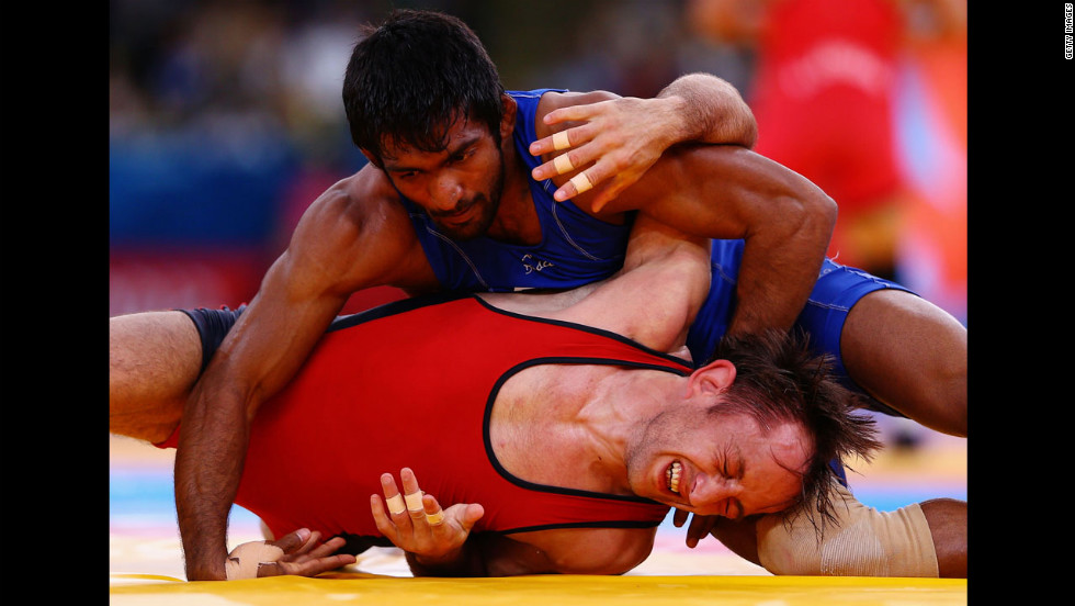 Indian wrestler Yogeshwar Dutt, in blue, and Bulgarian wrestler Anatolie Ilarionovitch Guidea, meet in the men's freestyle wrestling qualification match.