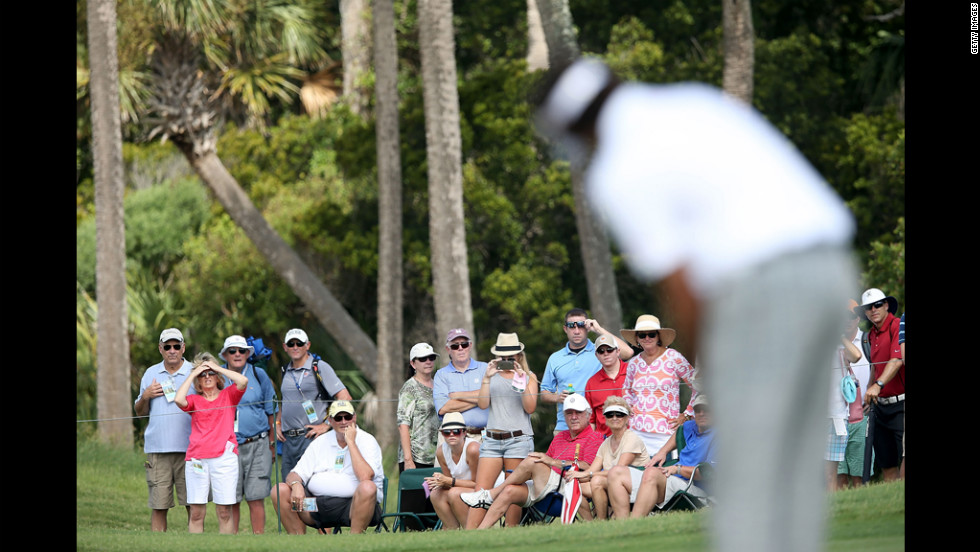 Spectators look on as Bubba Watson putts on the first green.