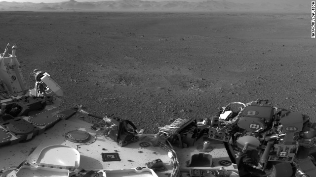 This mosaic image shows part of the left side of NASA's Curiosity rover and two blast marks from the descent stage's rocket engines. The images that were used to make the mosaic were obtained by the rover's Navigation cameras on Aug. 7 PDT (Aug. 8 EDT). The rim of Gale Crater is the lighter colored band across the horizon. The back of the rover is to the left. The blast marks can be seen in the middle of the image. Several small bits of rock and soil, which were made airborne by the rocket engines, are visible on the rover's top deck.