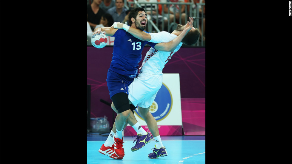 Nikola Karabatic, No.13 of France, is defended by Drago Vukovic, No.14 of Croatia, during the men's handball semifinal game between France and Croatia.