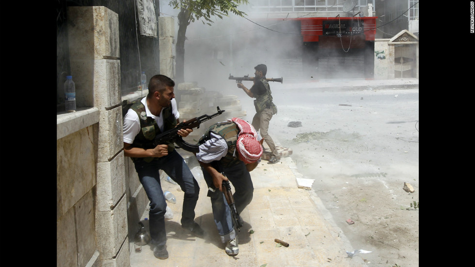 A Free Syrian Army fighter fires an RPG as a Syrian army tank shell hits a building across a street during heavy fighting in central Aleppo on Saturday, August 11.