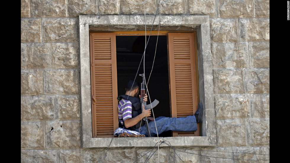 A Free Syrian Army fighter sits on a window sill as he holds an AK-47 rifle in central Aleppo.
