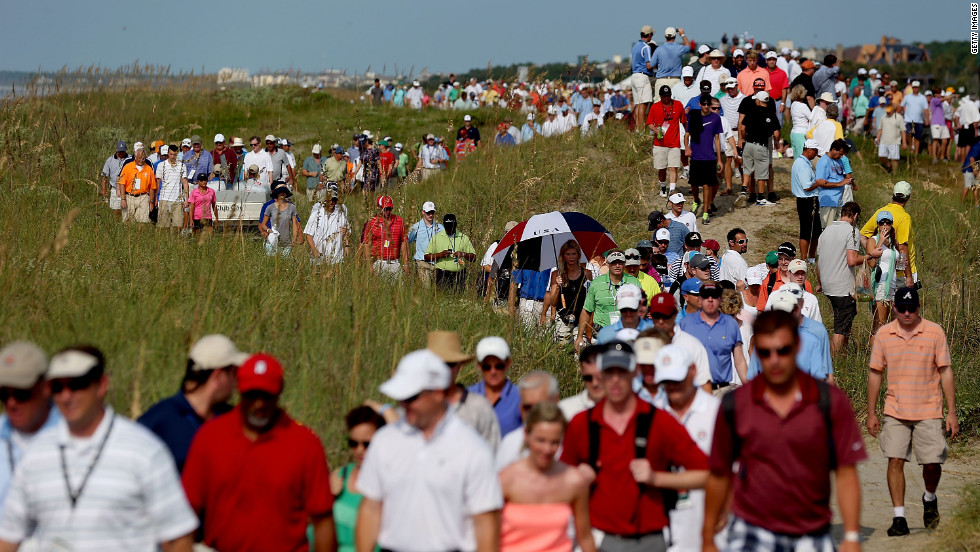 Spectators file along the course near the 16th hole to stake out a position for viewing.